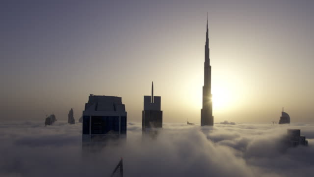 Timelapse fog drifts between skyscrapers as sun rises behind Burj Khalifa, Dubai