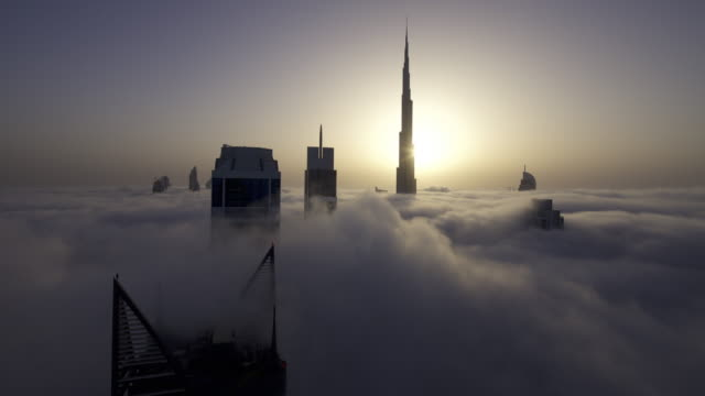 timelapse fog drifts between skyscrapers as sun rises behind burj khalifa, dubai - famous place stock videos & royalty-free footage