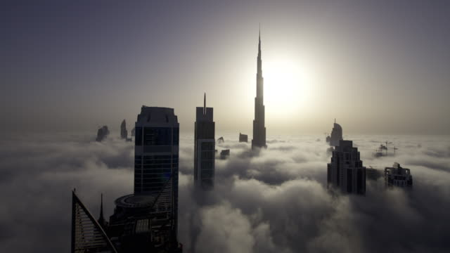 vidéos et rushes de timelapse fog drifts between skyscrapers as sun rises behind burj khalifa, dubai - élevé