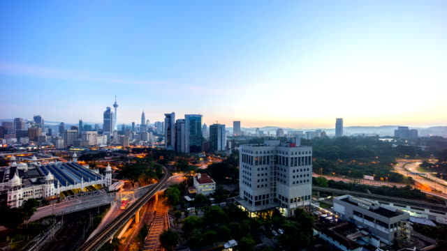 timelapse footage of a beautiful sunrise of Kuala Lumpur city view from rooftop of a building with moving vehicle, clouds and sunlight burst