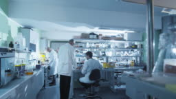 Timelapse footage of a team of scientists in white coats that are working in a modern laboratory.