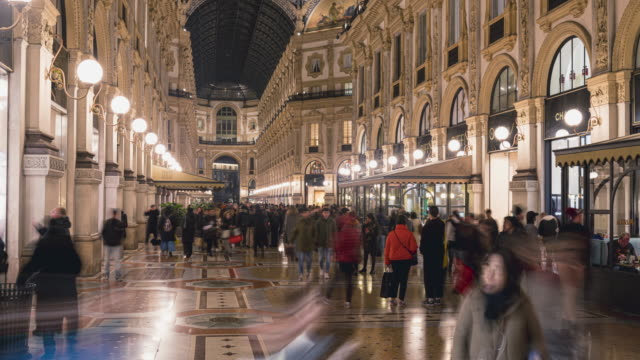 timelapse footage of people walk on duomo square near the famous vittorio emanuele shopping gallery, milan city, italy. - piazza video stock e b–roll