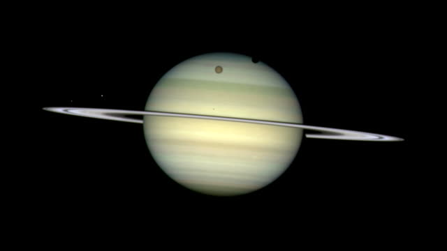 timelapse footage showing four of saturn's moons, as they circle the giant ringed planet, casting shadows on its cloud tops. imaged by the hubble space telescope in february 2009. - titan moon stock videos & royalty-free footage
