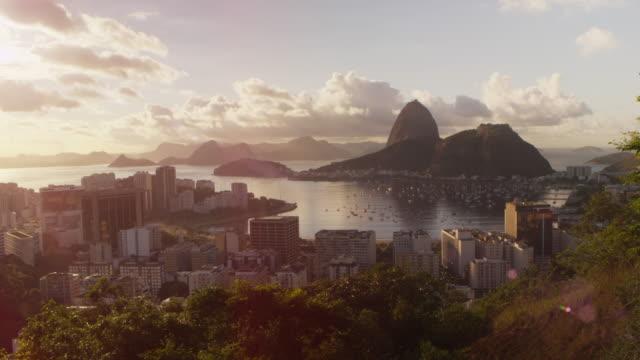 vídeos de stock, filmes e b-roll de time-lapse footage with solar flares of rio, sugarloaf mountain, and botafogo bay. - baía