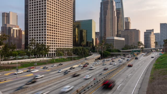 time-lapse freeway traffic at los angeles downtown sunset - motorway stock videos & royalty-free footage