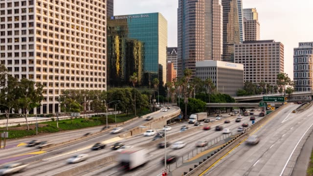 time-lapse freeway traffic at los angeles downtown sunset - autostrada interstatale americana video stock e b–roll