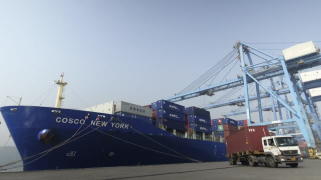 timelapse gantry cranes load shipping containers onto trucks from the cosco new york container ship docked at the jawaharlal nehru port operated by... - maharashtra stock-videos und b-roll-filmmaterial