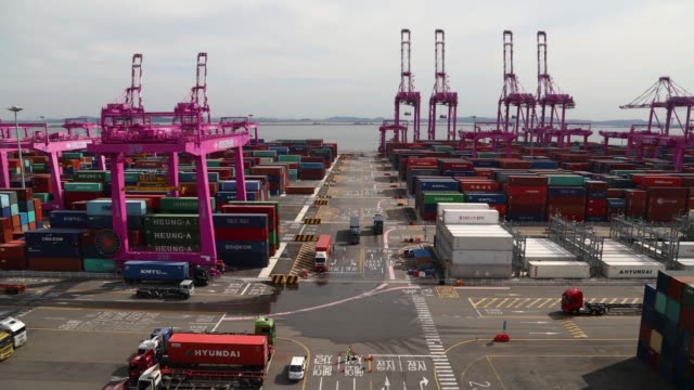stockvideo's en b-roll-footage met timelapse gantry cranes move among stacked shipping containers as container trucks drive past at the sun kwang newport container terminal in incheon... - incheon