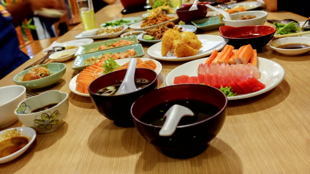timelapse group of friend eating with chopsticks takes sushi from a plate in a japanese restaurant. - sushi video stock e b–roll