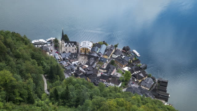 timelapse high angle scenic view of famous hallstatt mountain village and boat port on a rainy day in summer covering much cloudy.  one of the travel destinations in austrian culture and the european alps and lakeshore in europe. - austrian culture stock videos & royalty-free footage