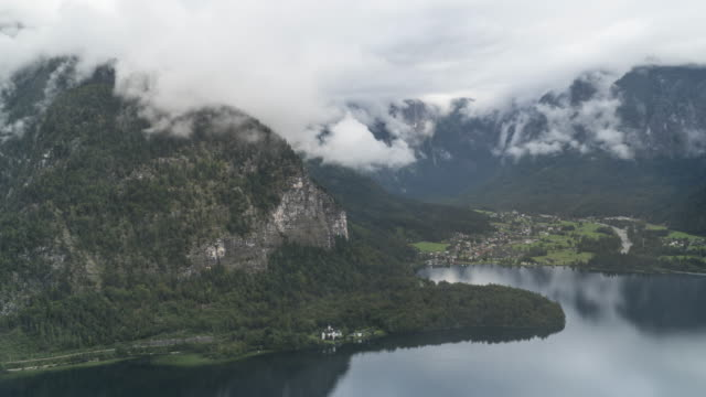 timelapse high angle scenic view of famous obertraun mountain village and boat port on a rainy day in summer covering much cloudy.  one of the travel destinations in austrian culture and the european alps and lakeshore in europe. - austrian culture stock videos & royalty-free footage
