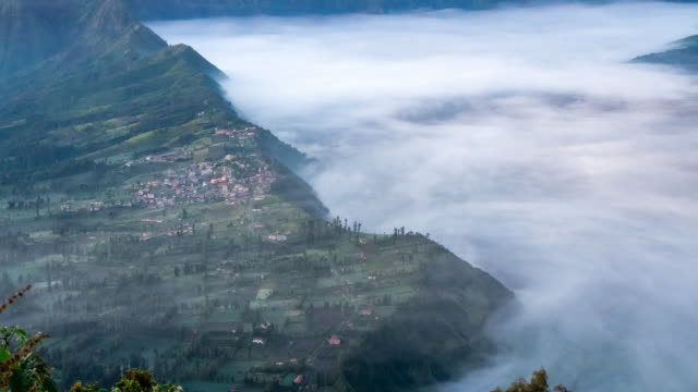 Time-lapse High angle shot Fog over top village near at mount bromo