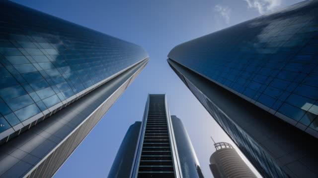4k timelapse high modern finance skyscrapers over blue sky,abu dhabi,uae - large stock videos & royalty-free footage