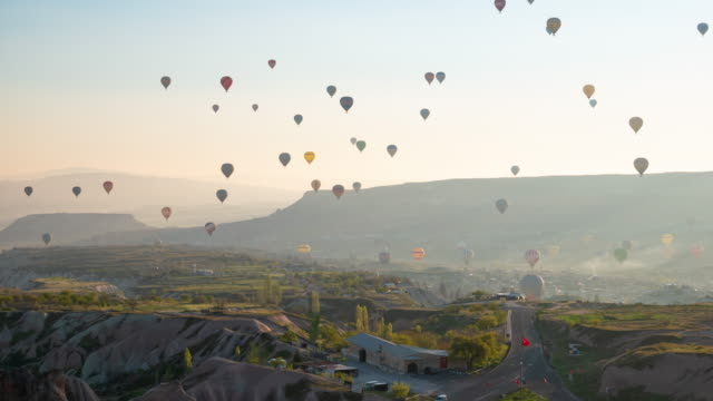 time-lapse : hot air balloons in cappadocia passing over the valley göreme in turkey with  the early morning, 4k resolution. - ignition stock videos & royalty-free footage
