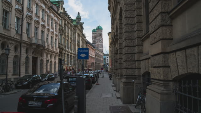 Timelapse / Hyperlapse towards famous Frauenkirche in Munich, Bavaria, Germany - Push in shot in a narrow street on the sidewalk