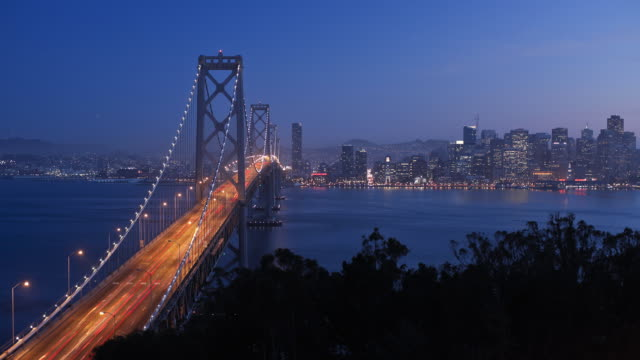 time-lapse illuminated view of san francisco bay bridge and city skyline viewed from treasure island, san francisco, california, united states of america - san francisco oakland bay bridge bildbanksvideor och videomaterial från bakom kulisserna