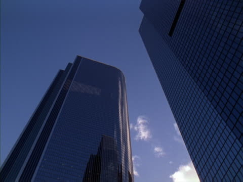 Timelapse image of  clouds above glass buildings