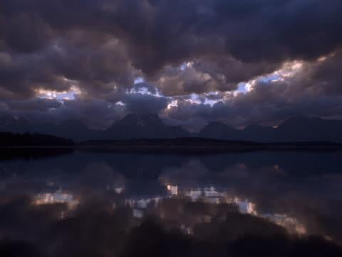 timelapse image of low clouds,mountains, and lake at sunset. - teton range stock videos & royalty-free footage