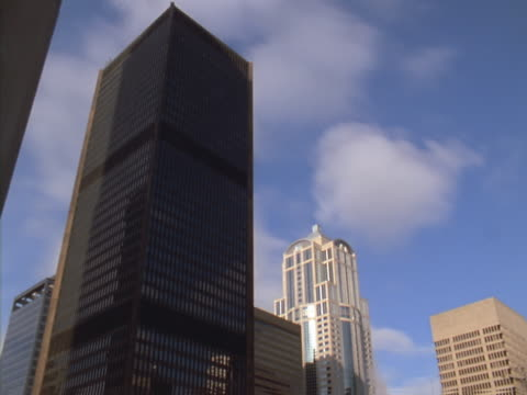 timelapse image of white clouds in blue sky passing over tall city buildings - artbeats 個影片檔及 b 捲影像