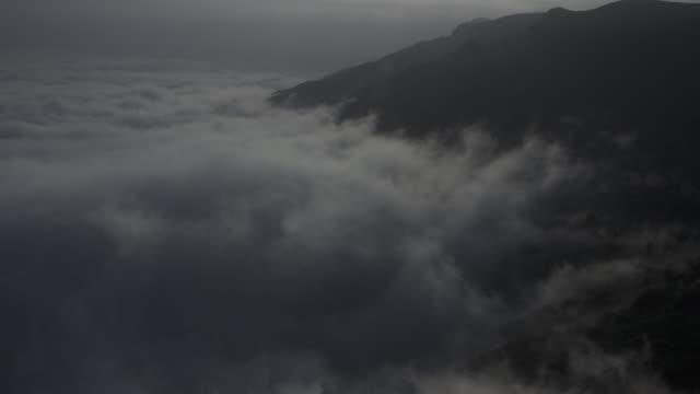 timelapse khareef monsoon mist swirls over mountainous coast, oman - monsoon stock videos & royalty-free footage