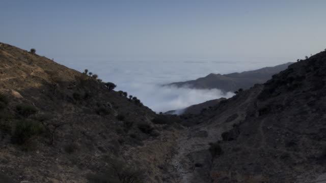 Timelapse Khareef monsoon mist swirls over mountainous coast, Oman