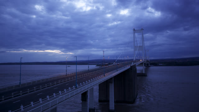 timelapse lights come on as night falls over severn bridge, uk - river severn stock videos & royalty-free footage