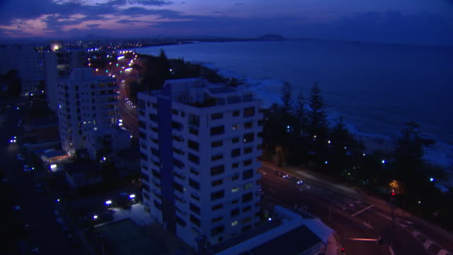 vidéos et rushes de timelapse - locked off high wide shot at dusk / looking northwest over row of beachfront apartment blocks and foreshore coastline, towards the coral... - phare de véhicule