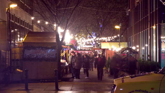 Time-Lapse Manchester Christmas market hustle and bustle with lights and general activity.