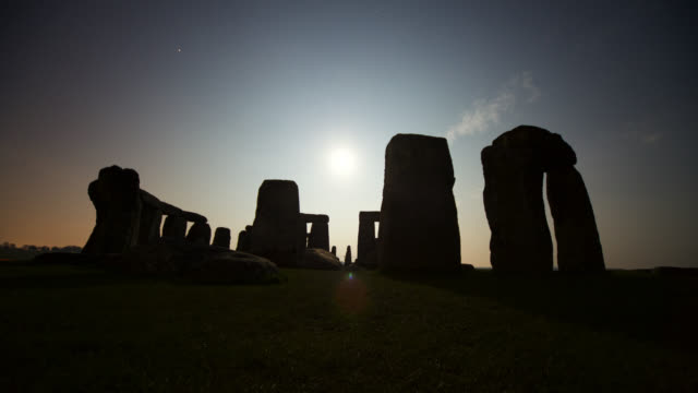 Timelapse moon and clouds track over prehistoric Stonehenge monument, Wiltshire, UK