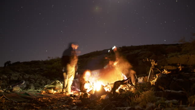 timelapse moon and stars track over men and campfire in desert, oman - adults only videos stock videos & royalty-free footage