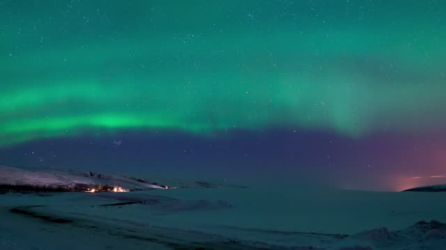 4K Timelapse movement of strong bright Aurora Borealis above the snow covered on the field mountain, northern Iceland