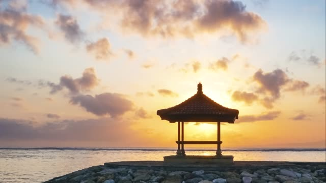 vídeos de stock e filmes b-roll de time-lapse moving cloud and sunshine over view pavilion near sea at karang beach, sanur in bali, indonesia for sunrise viewpoint - bali