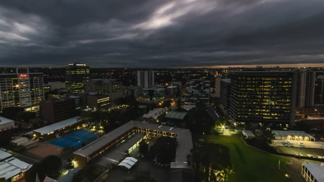 Timelapse Night High Shot Looking east building lights on Lights turn off as it moves into dawn Construction crane midshot Arthur Phillip High School...