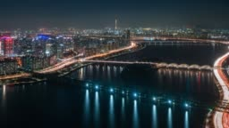Timelapse night scene of business district in Seoul city with traffic of car on bridge cross over Han river into Lotte World Tower in Seoul city, South Korea