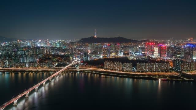 timelapse nachtszene yeouido geschäftsviertel mit verkehr autos auf brücke überqueren han-fluss in n seoul tower in seoul city, südkorea - besichtigung stock-videos und b-roll-filmmaterial