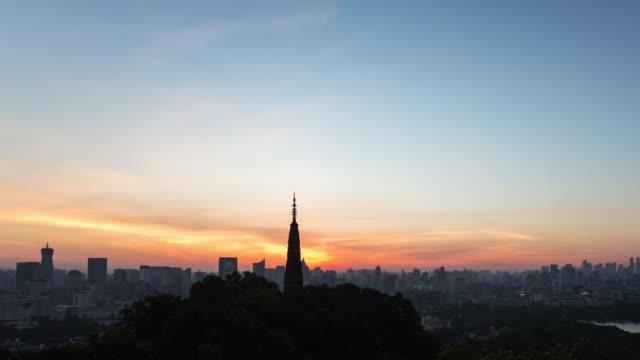 4k time-lapse night to day:an orange sun glows on the horizon of the hangzhou skyline,china - turmspitze stock-videos und b-roll-filmmaterial
