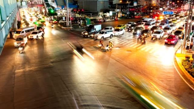 zeitraffer nachtverkehr auf der ratchadaphisek straße an der asoke kreuzung in bangkok stadtzentrum von thailand. - länge stock-videos und b-roll-filmmaterial