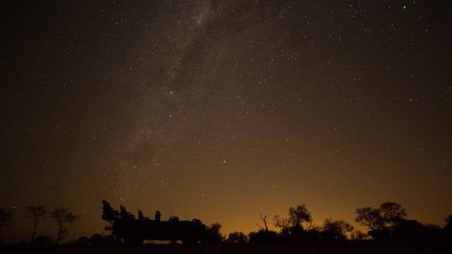 Timelapse of a 4x4 safari vehicle silhouetted against the night sky