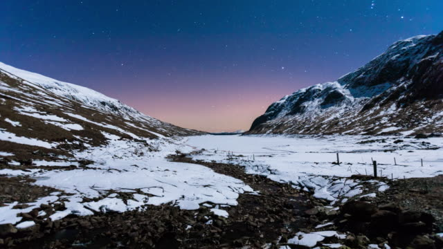 stockvideo's en b-roll-footage met time-lapse of a frozen hydroelectric dam stream and lake in scotland with the clear night sky stars and movement of the mountain‰ûªs shadow cast by the moon - astronomie
