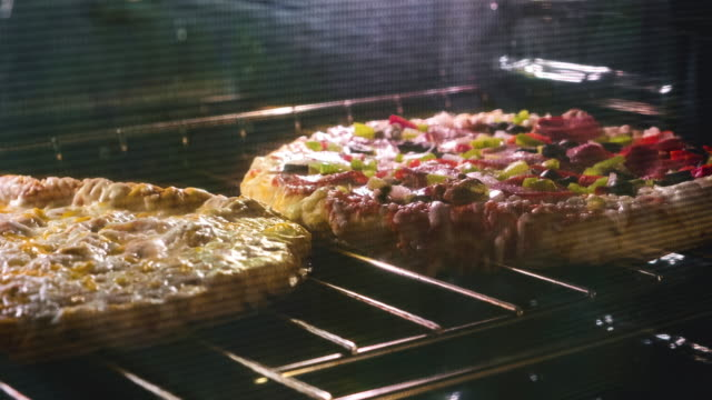 timelapse of a frozen pizza in the oven - cibi surgelati video stock e b–roll