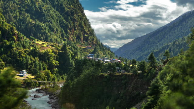 Time-lapse of a Himalayan valley with a river and a small village.
