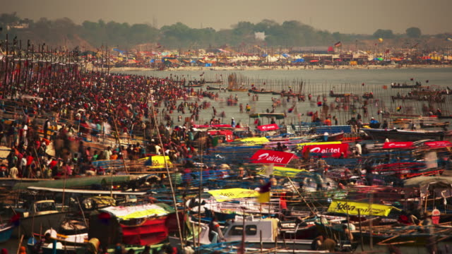 timelapse of a huge crowd of people standing on busy riverbank during the hindu kumbh mela celebrations in india - uttar pradesh stock videos and b-roll footage