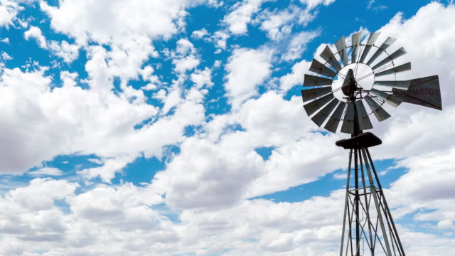 vidéos et rushes de timelapse of a karoo windmill blowing in the wind while clouds pass ahead - karoo