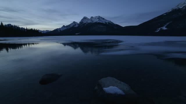 Time-Lapse of a mountain sunrise on a frozen alpine lake