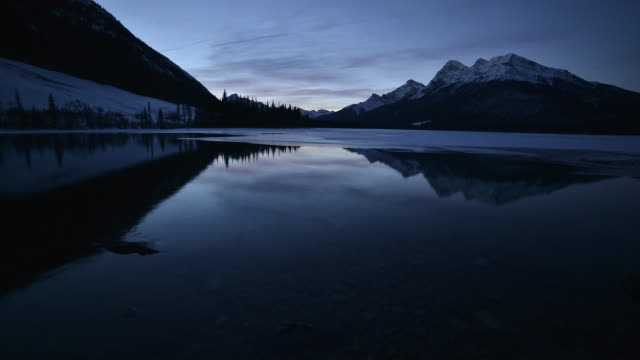 Time-Lapse of a mountain sunrise on a frozen alpine lake