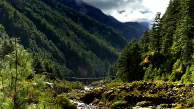 stockvideo's en b-roll-footage met time-lapse of a river and a trail in a himalayan valley. cropped. - valley