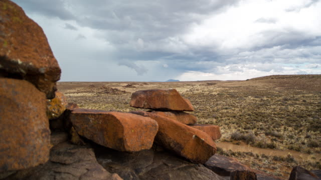 vidéos et rushes de timelapse of a rocky karoo landscape with storm clouds gathering as the camera moves in behind rocks in the foreground - karoo