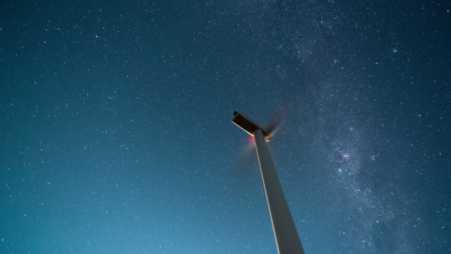 timelapse of a sky of stars moving behind a wind turbine - windenergie stock-videos und b-roll-filmmaterial