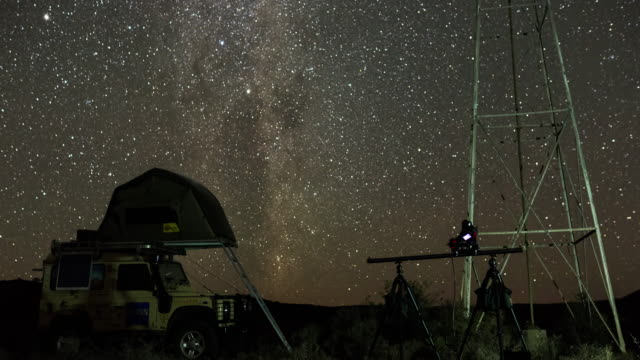 timelapse of a vehicle, tent and camera below a karoo windmill at night - karoo bildbanksvideor och videomaterial från bakom kulisserna