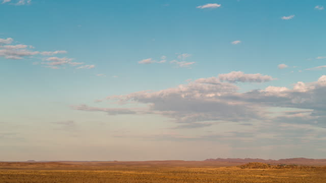 Timelapse of a wide open Karoo landscape just after sunrise with scattered clouds moving along a blue sky